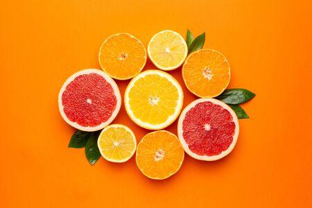 Citruses fruits on orange background, fruit flatlay, summer minimal compositon with grapefruit, lemon, mandarin and orange. Summer color , harvest top view, cutting fruits