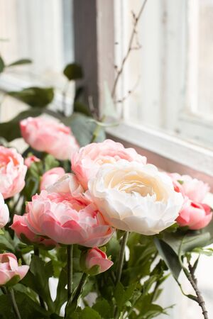 Artificial pink flowers on a background of a white brick wall copy space side view