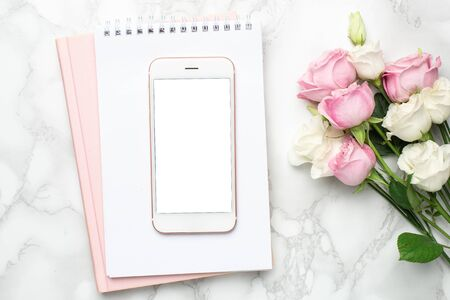 Mobile phone with pink and white roses flowers on marble background.Minimalistic composition for the holidays,valentines day and womens day. Stock Photo