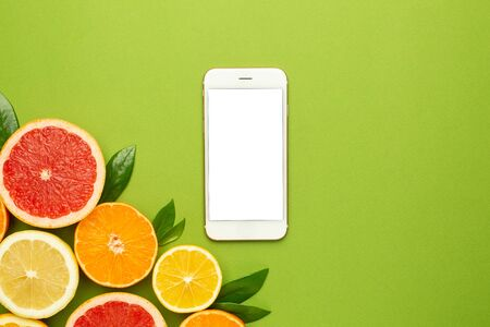 Mobile phone and citruses on an green background, technology and fruit flatlay, summer minimal compositon with grapefruit, lemon, mandarin and orange top view