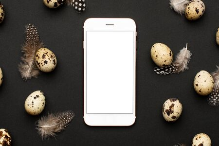 Mobile phone and quail eggs with feathers on a black background. Holiday easter, minimalistic black composition top view