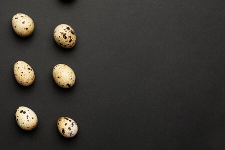 Quail eggs close-up on a black background with copyspace. Holiday easter, minimalistic black composition Foto de archivo