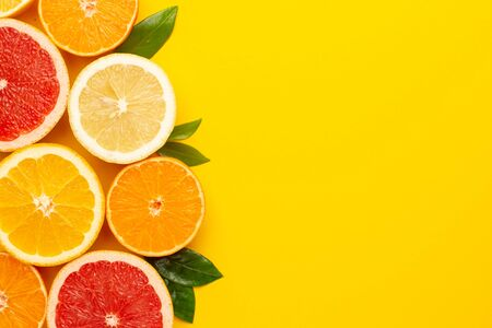 Citruses fruits on yellow background with copyspace, fruit flatlay, summer minimal compositon with grapefruit, lemon, mandarin and orange top view