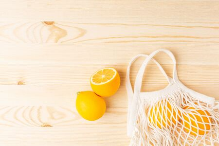 Lemons in cotton shopping eco friendly bag on wooden background top view. Help for colds, natural remedies for the disease Zdjęcie Seryjne