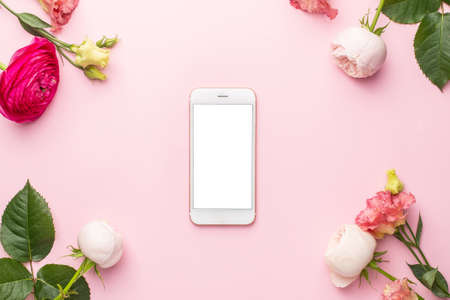 Mobile phone and Ranunculi pink flower bouquet on pink background with copyspace top view