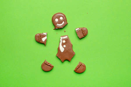 Broken chocolate figurine of a gingerbread man on a green background new year and Christmas holidays top view