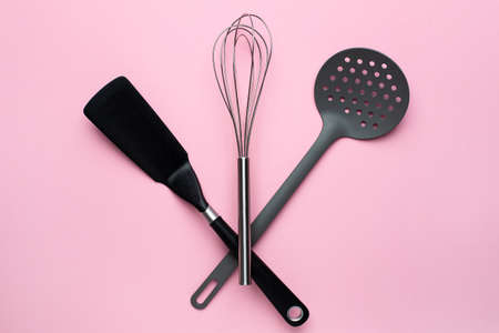 Kitchen accessories spatula whisk on a pink background, female cooking top view
