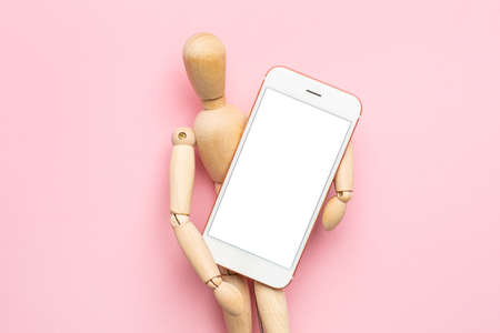 A wooden figure of a man with a mobile phone on a pink background top view