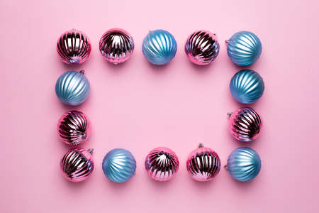 Shiny Christmas blue and pink balls for decoration on pink background with copyspace, new year ball top view
