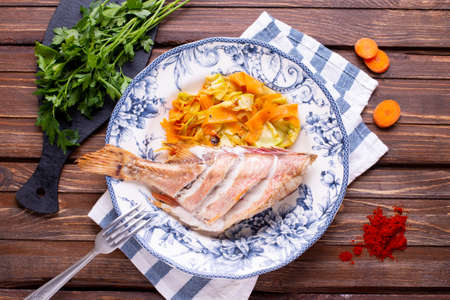 Baked sea bass with vegetables on the table, restaurant dish on a wooden background top view