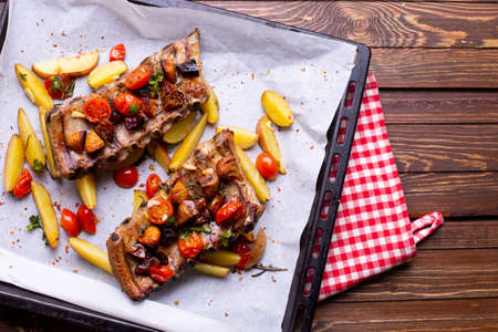 Pork ribs with vegetables on a wooden background, cooking at home top view Zdjęcie Seryjne
