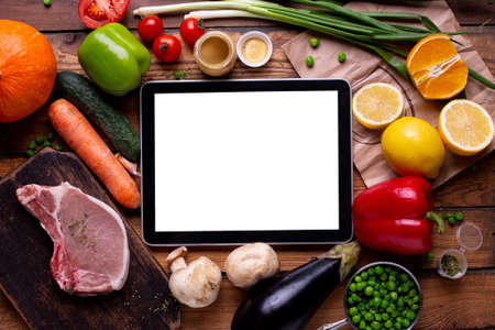 Electronic tablet white empty screen temperate with meat and different vegetables on a wooden background top view