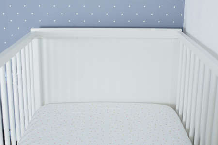 Baby bed crib white color in white bedroom side view without kid