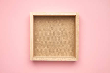 A empty wooden box isolated on pink pastel background top view.