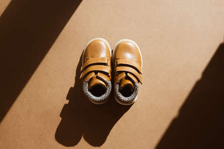A pair of small leather shoe on a light, brown background with sun shadow. Warm, fur-lined childrens shoes with laces. Concept of the coming autumn and winter. Zdjęcie Seryjne