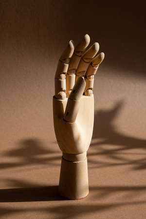 A hand of wood doll make fingers to touch, direct, move on brown background at the studio with dark shadows