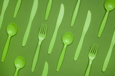 Green plastic forks, spoons, knifes on green paper. Set of plastic cutlery in different spoons forks knives and eco-friendly plastic concept. Flat lay. Horizontal. Close-up top