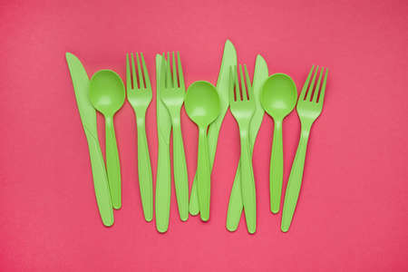 Green plastic forks, spoons, knifes on pink paper. Set of plastic cutlery in different spoons forks knives and eco-friendly plastic concept. Flat lay. Horizontal. Close-up top view