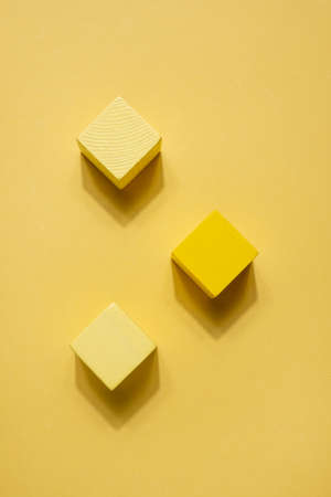 Yellow geometrical figures still life composition. Wooden game cube objects on yellow background. Platonic solids figures, simplicity concept top view with shadow Zdjęcie Seryjne