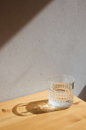A glass with clean clear water and sharp shadows stands on a wood table on gray wall background side view Zdjęcie Seryjne