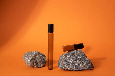 Brown glass bottle on stone on orange background. Natural Organic Spa Cosmetic concept Front view