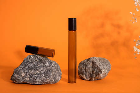 Brown glass bottle on stone and flowers on orange background. Natural Organic Spa Cosmetic concept Front view Zdjęcie Seryjne