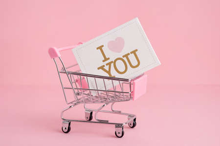 Small shopping market trolley on a pink background, copy space, shopping and love concept side view Stockfoto