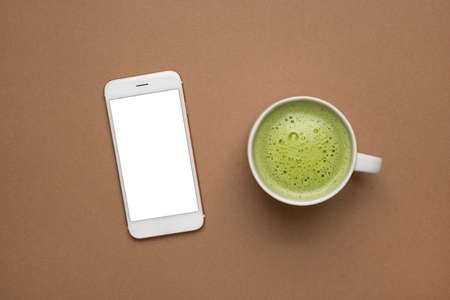 Mobile phone mock up and hot green tea late with modern style and delicious on light brown background, matcha texture macro top view