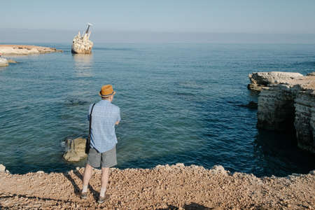Man traveling near ocean in Cyprus . Man lifestyle concept summer vacations outdoor. Beautuful nature landscape on the background back view