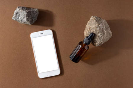 One brown serum glass bottle with pipette and mobile phone mock up , stone and technology composition on brown background. Natural Organic Spa Cosmetic concept top view