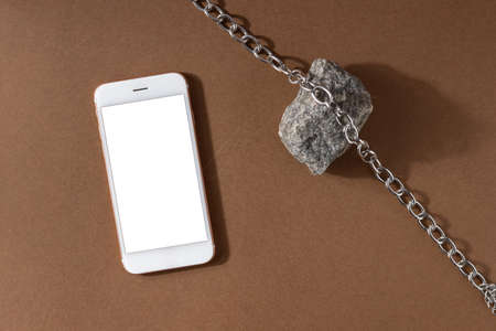 Minimalist beige brown life composition with natural material and technology - mobile phone, stone and steel chain, abstract modern art design concept top view