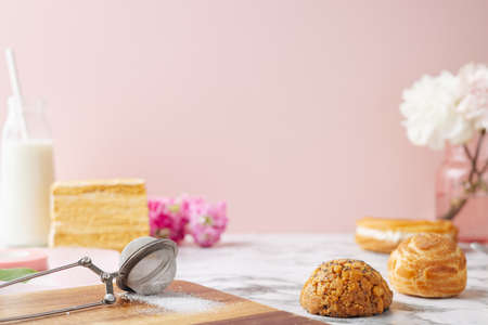 Profiteroles with custard, Piece of delicious cake on the marble table.Sweet dessers side view. Space for text on pink Stockfoto
