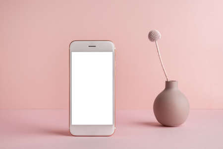 Mobile phone with white screen and dry flower in vase on pink background with dark shadows. Trend, minimal concept with copyspace side view Stockfoto