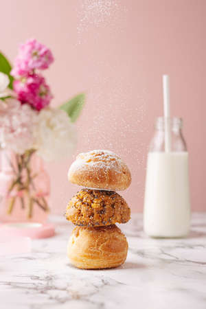 Homemade profiteroles with custard covered sugar powder on marble table on pink background with flowers and milk vertical