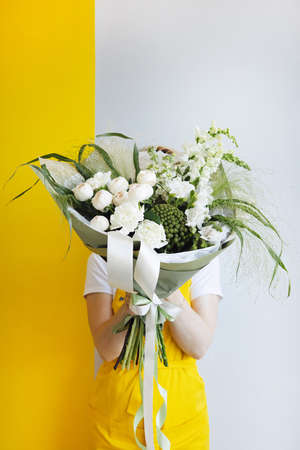 Beautiful modern wedding bouquet with white roses in hand . Flower shop and delivery concept. Holiday present, mother day side vertical