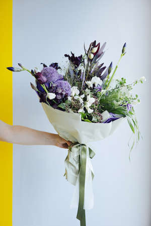 Beautiful purple flower bouquet in hands on the gray wall background, modern flower shop delivery side view Stockfoto