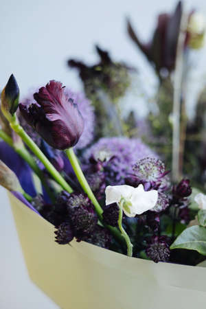 Beautiful purple flower bouquet on the gray wall background, modern flower shop delivery side view vertical
