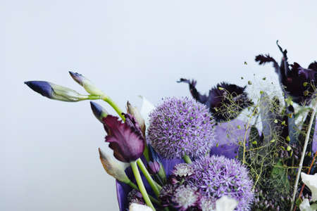 Beautiful purple flower bouquet on the gray wall background, modern flower shop delivery side view