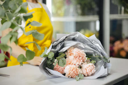 Small business. Florist unfocused in flower shop. Floral design studio, making bouquet. Flowers delivery, creating order side view