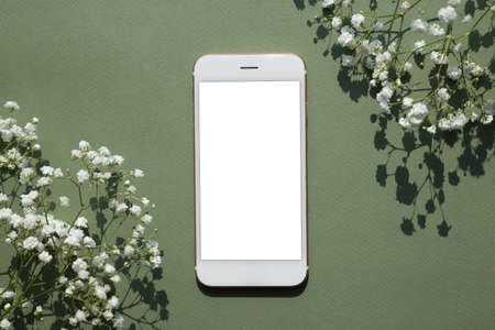 Mobile phone mock up on a pastel green background decorated with white small flowers top view Stockfoto