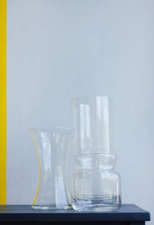 Three empty glass vases on gray yellow background. Antique interior decoration objects vertical shot