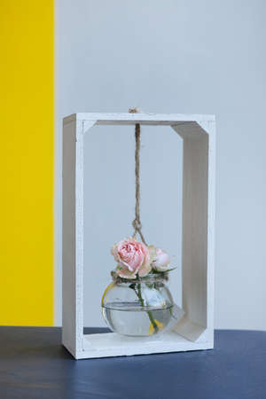 Glass vase with small rose flower on gray yellow background. Antique interior decoration object vrtical shot