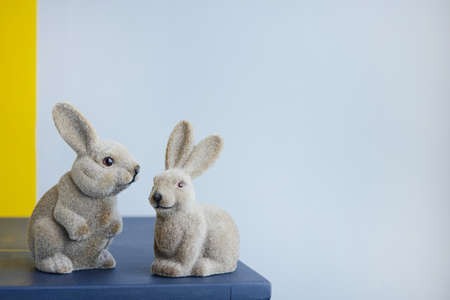 Ceramic easter hares, vintage figurine rabbit on a gray wall background with copyspace side view Stockfoto