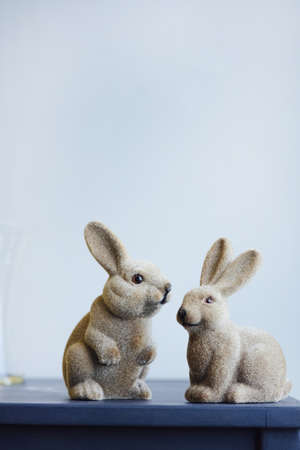 Ceramic easter hares, vintage figurine rabbit on a gray wall background vertical shot Stockfoto