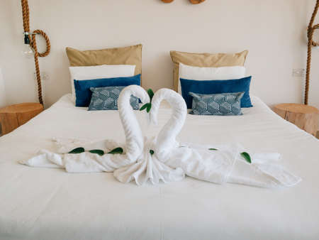 Towel white swans couple kiss heart shape on bed sheet hotel guest room decoration background side view