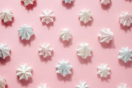Pink and white meringue, zephyr, marshmallow, on pink background, selective focus side view