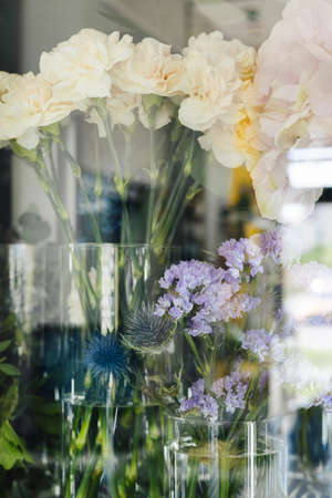Flower shop concept. Different fresh spring flowers in refrigerator room for flowers close up. Bouquets on shelf, florist business vertical