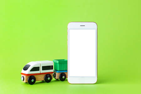 Train children toy and mobile phone with white screen, preschool kids game and technology. Wooden colorful blocks construction on green color background side view