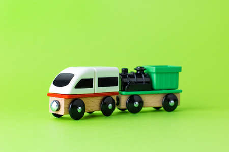 Train children toy, preschool kids game. Locomotive and carriages, wooden colorful blocks construction on green color background side view Stockfoto