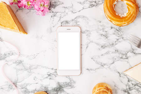 Homemade desserts, cake, profitroles and mobile phone with white screen . Eclairs with cream, French dessert and flowers on marble table on pink background top view